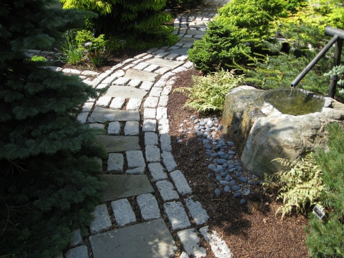 fountain-with-copper-spout next to a path to meditation